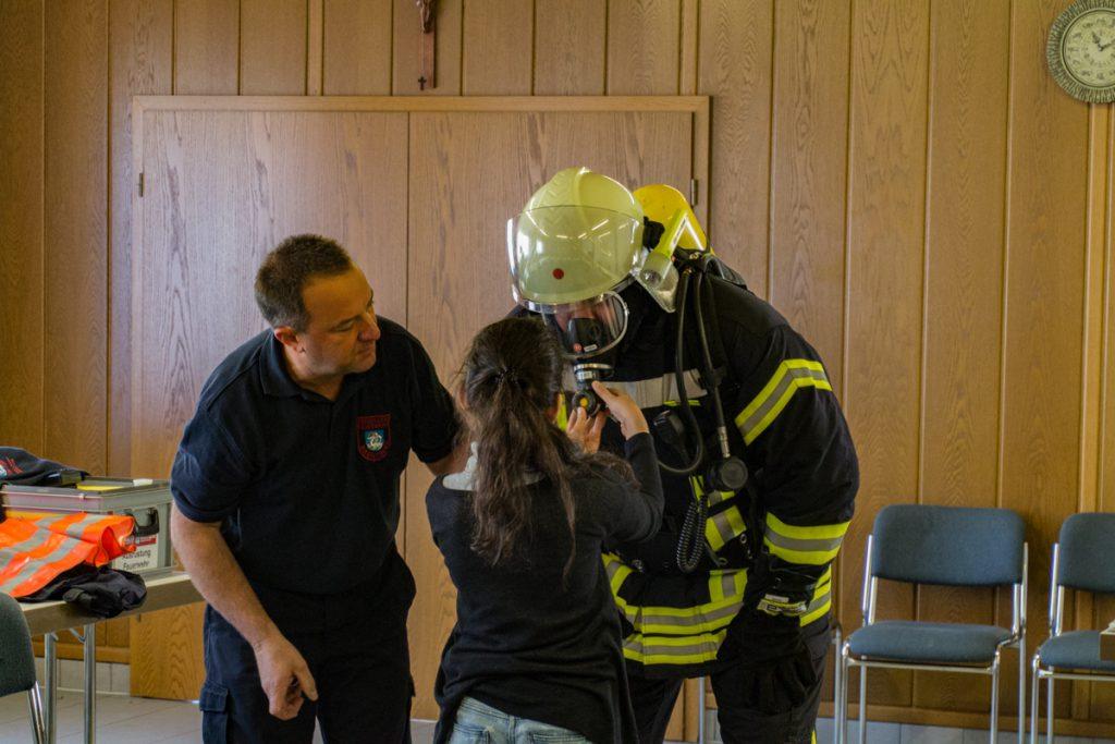 Die Kinder helfen beim Anlegen des Atemschutzgerätes
